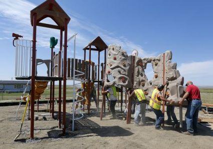 Montana - Des ouvriers à pied d'oeuvre pour terminer le terrain de jeu de la tribu Chippewa Cree, un équipement financée par la fondation Original Americans Foundation